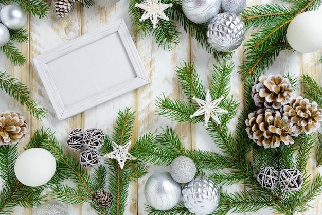 Marco de fotos entre la decoración de navidad, con bolas blancas y estrellas sobre una mesa de madera blanca. vista superior, marco para copiar espacio.