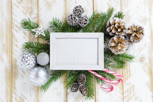 Marco de fotos entre la decoración de navidad, con bolas blancas y piñas en una mesa de madera blanca. vista superior, marco para copiar espacio
