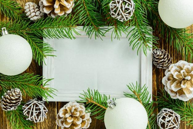 Marco de fotos entre la decoración de navidad, con bolas blancas y piñas en una mesa de madera marrón. vista superior, marco para copiar espacio.