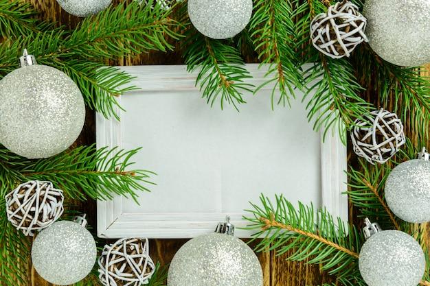 Marco de fotos entre la decoración de navidad, con bolas blancas sobre una mesa de madera marrón. vista superior, marco para copiar espacio.