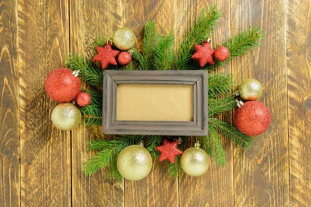Marco de fotos entre la decoración de navidad, con bolas de color dorado y estrellas sobre una mesa de madera marrón. vista superior, marco para copiar espacio.
