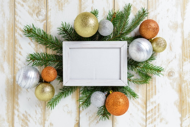 Marco de fotos entre la decoración de navidad, con bolas de color naranja y blanco sobre una mesa de madera blanca. vista superior, marco para copiar espacio.