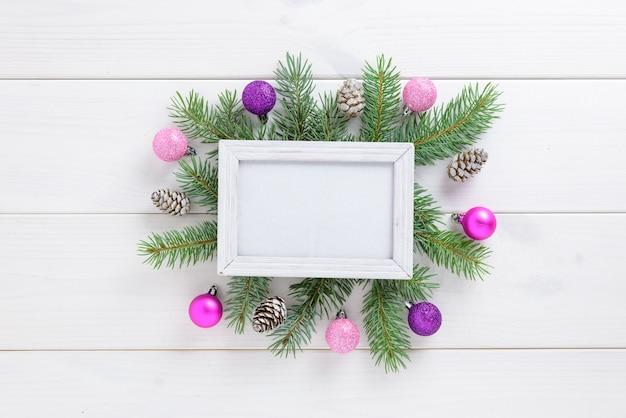 Marco de fotos entre la decoración de navidad, con bolas de color rosa y piñas en una mesa de madera blanca. vista superior, marco para copiar espacio