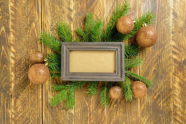 Marco de fotos entre la decoración de navidad, con bolas en una mesa de madera marrón. vista superior, marco para copiar espacio.