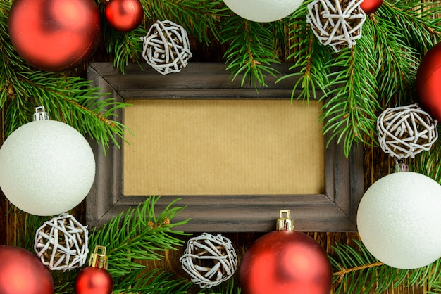 Marco de fotos entre la decoración de navidad, con bolas rojas y blancas sobre una mesa de madera marrón. vista superior, marco para copiar espacio.