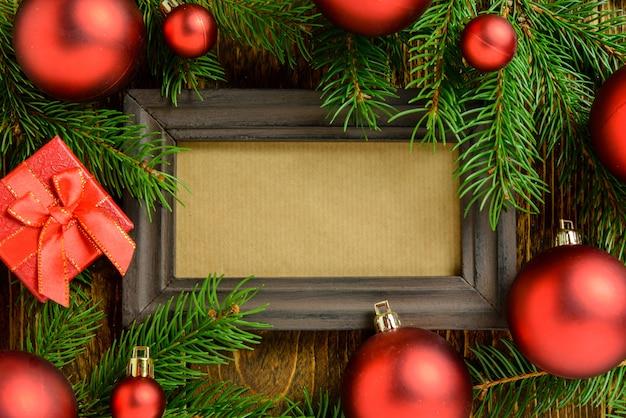 Marco de fotos entre la decoración de navidad, con bolas rojas y caja de regalo sobre una mesa de madera marrón. vista superior, marco para copiar espacio.
