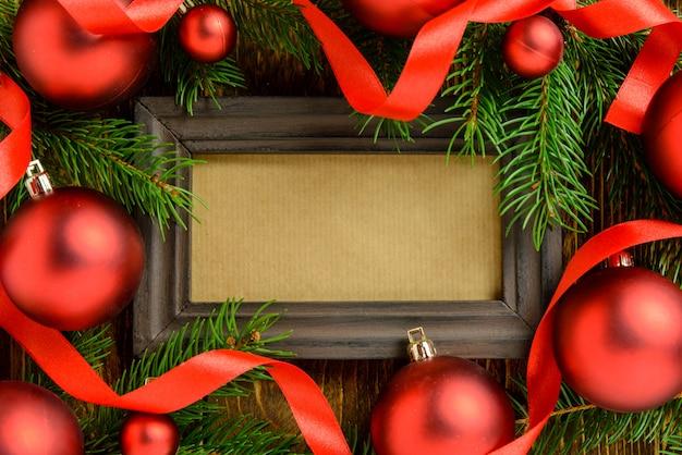 Marco de fotos entre la decoración de navidad, con bolas rojas y cintas sobre una mesa de madera marrón. vista superior, marco para copiar espacio.