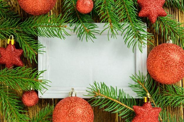 Marco de fotos entre la decoración de navidad, con bolas rojas y estrellas sobre una mesa de madera marrón. vista superior, marco para copiar espacio.
