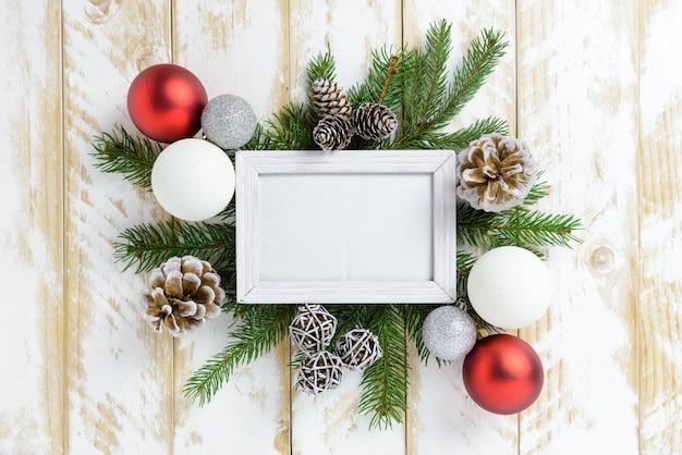 Marco de fotos entre la decoración de navidad, con bolas rojas y piñas en una mesa de madera blanca. vista superior, marco para copiar espacio.
