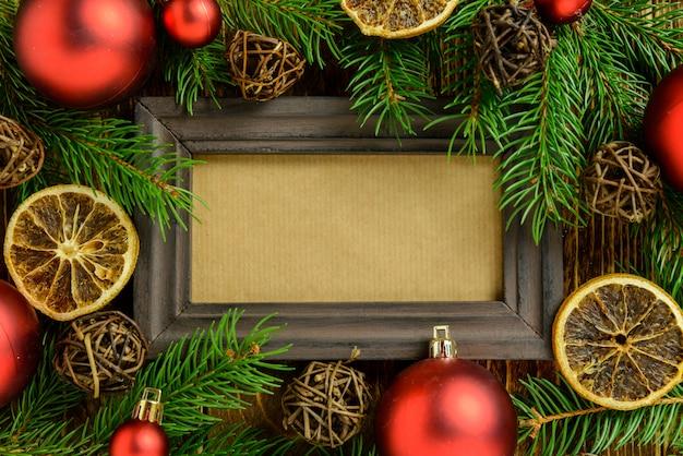 Marco de fotos entre la decoración de navidad, con bolas rojas sobre una mesa de madera marrón. vista superior, marco para copiar espacio.