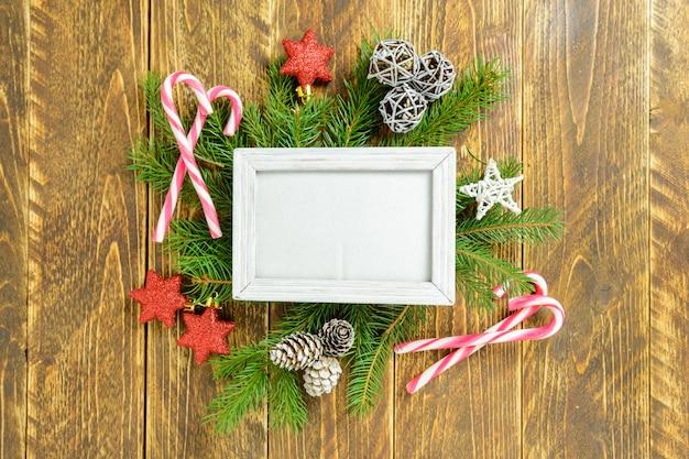 Marco de fotos entre la decoración de navidad, con estrellas y bastón de caramelo sobre una mesa de madera marrón. vista superior, marco para copiar espacio.