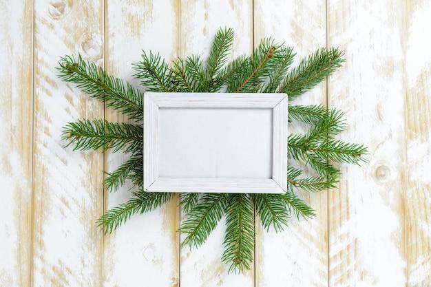 Marco de fotos entre la decoración de navidad, rama de pino verde sobre una mesa de madera blanca. vista superior, marco para copiar espacio.