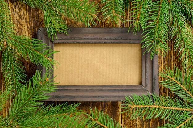 Marco de fotos entre la decoración de navidad, rama de pino verde sobre una mesa de madera marrón. vista superior, marco para copiar espacio.