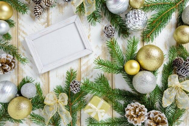 Marco de fotos entre decoración navideña, con bolas de color dorado y conos de pino sobre una mesa de madera blanca. vista superior, marco para copiar espacio.