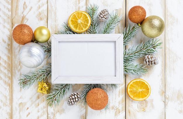 Marco de fotos entre decoración navideña, con bolas de color dorado y conos de pino sobre una mesa de madera blanca. vista superior, marco para copiar espacio
