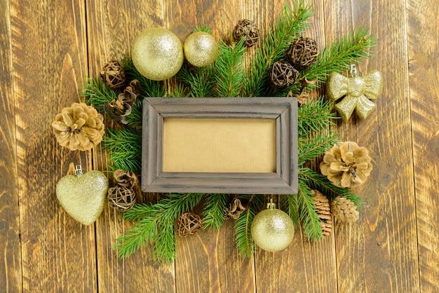 Marco de fotos entre decoración navideña, con bolas de color dorado y conos de pino sobre una mesa de madera marrón. vista superior, marco para copiar espacio.