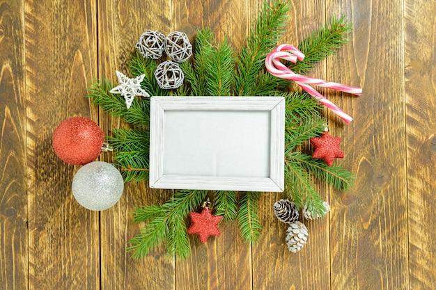 Marco de fotos entre decoración navideña, con bolas de colores y bastón de caramelo sobre una mesa de madera marrón. vista superior, marco para copiar espacio.