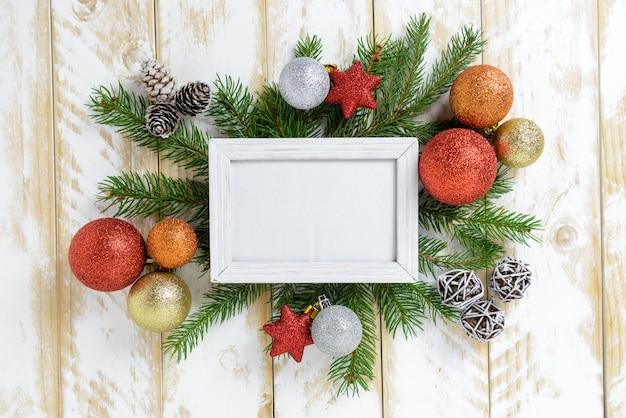 Marco de fotos entre decoración navideña, con bolas de colores y conos de pino sobre una mesa de madera blanca. vista superior, marco para copiar espacio.
