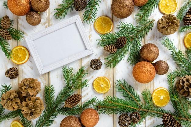 Marco de fotos entre decoración navideña, con bolas de colores y conos de pino sobre una mesa de madera marrón. vista superior, marco para copiar espacio.