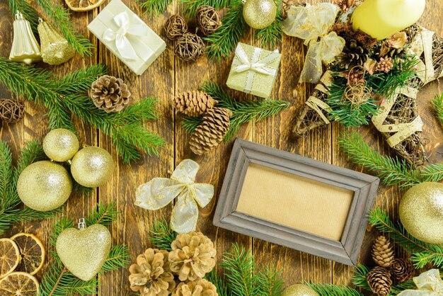 Marco de fotos entre decoración navideña, con diferentes adornos de color dorado sobre una mesa de madera marrón. vista superior, marco para copiar espacio.