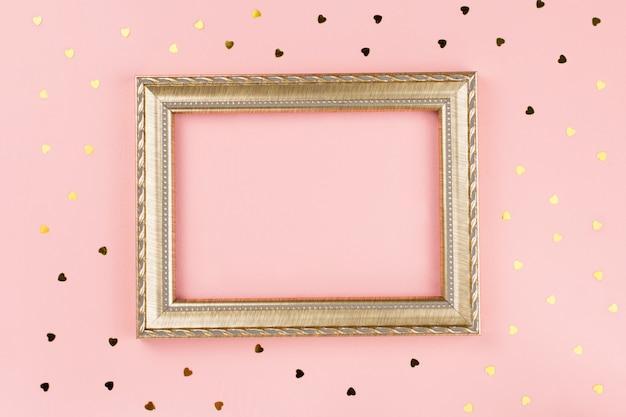 Marco de fotos dorado y confeti dorado sobre fondo rosa pastel
