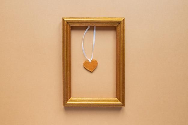 Marco de fotos dorado con corazón de madera en el interior.