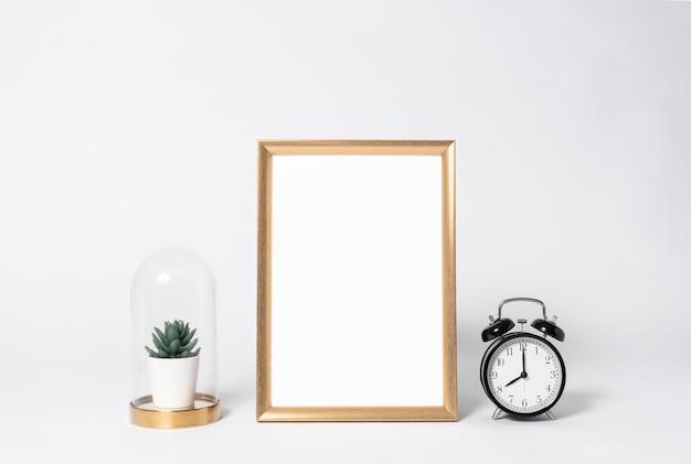Marco de fotos dorado maqueta y reloj elementos de decoración interior para el hogar.