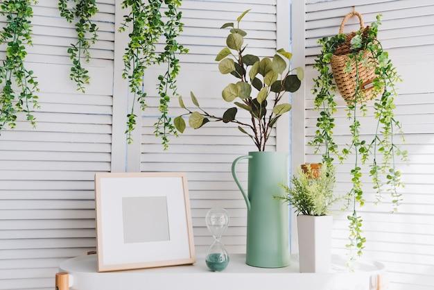 Marco de fotos, florero, reloj de arena, plantas y diversos objetos decorativos en una mesa