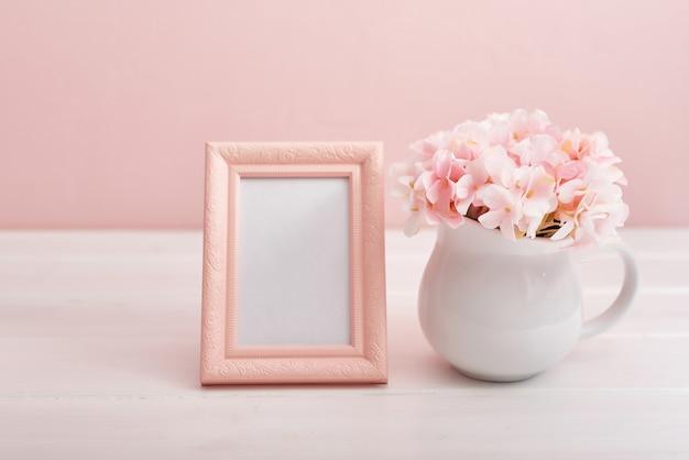 Marco de fotos y jarrón con flores.
