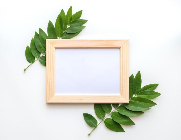 Marco de fotos de madera vacía con hojas verdes