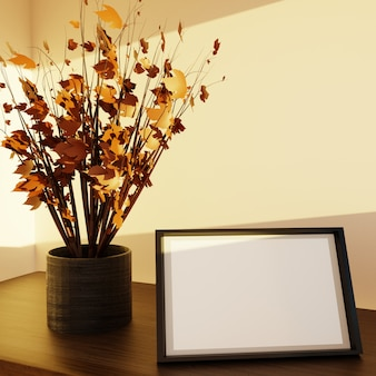 Marco de fotos en la mesa para maqueta con mini árbol de otoño bajo la luz solar