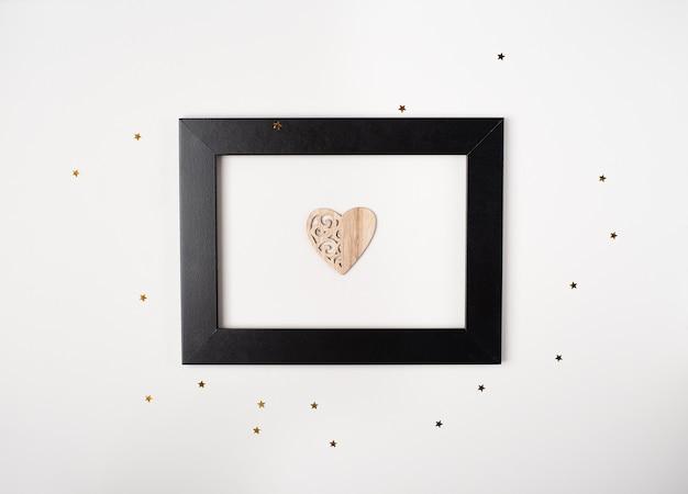 Marco de fotos negro con el corazón de madera en el interior sobre el fondo claro con pequeñas estrellas doradas