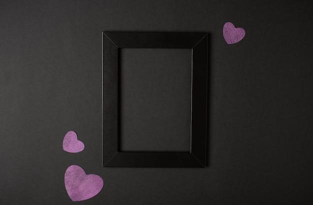 Marco de fotos negro con corazones rosas a los lados sobre fondo negro. vista plana endecha, superior. concepto de san valentín.