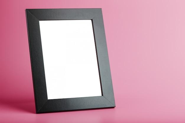 Marco de fotos negro con un espacio vacío sobre un fondo rosa.