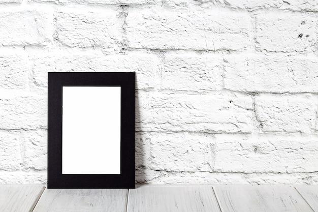 Marco de fotos negro vertical en la mesa de madera. maqueta con copia espacio