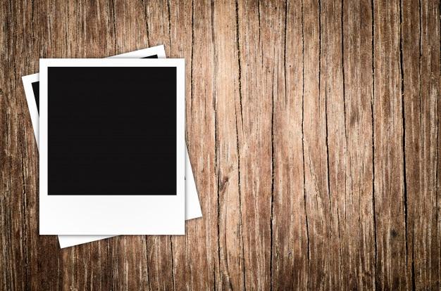 Marco de fotos polaroid sobre fondo de madera