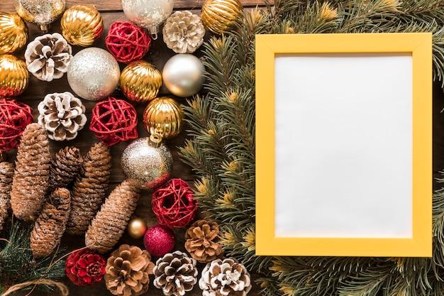 Marco de fotos entre ramas de abeto, enganches de adorno y bolas de navidad.