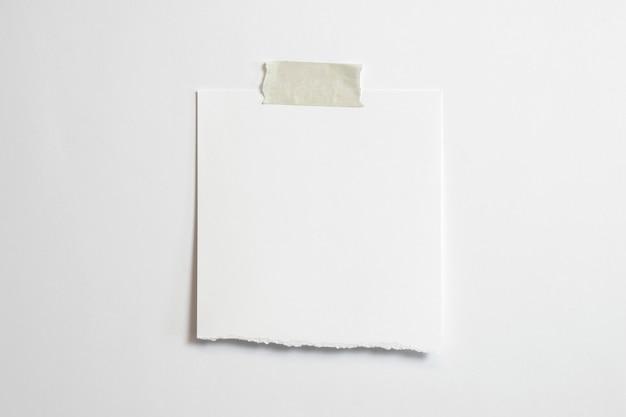 Marco de fotos rasgado en blanco con sombras suaves y cinta adhesiva aislado sobre fondo de papel blanco