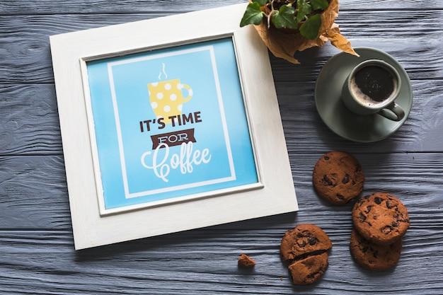 Marco de fotos con taza de café y galletas