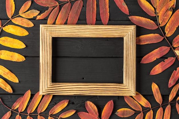 Marco de fotos vacío y coloridas hojas de otoño