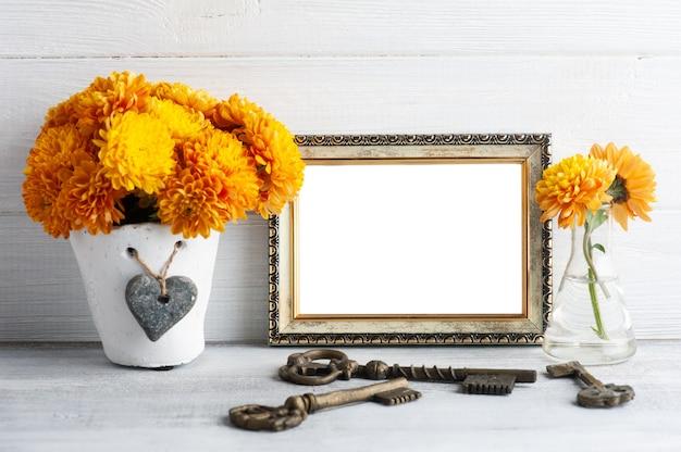 Marco de fotos vacío y flores de crisantemo naranja sobre mesa rústica blanca
