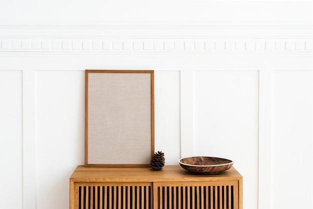 Marco grande en blanco sobre un aparador de madera en una sala de estar