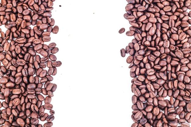 Marco de granos de café tostados aislados en blanco uso como fondo o textura