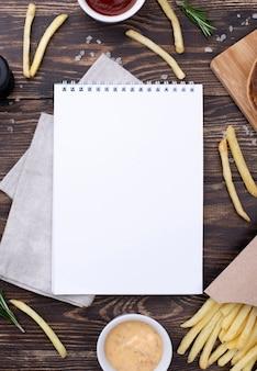 Marco de hamburguesas y papas fritas al lado del cuaderno