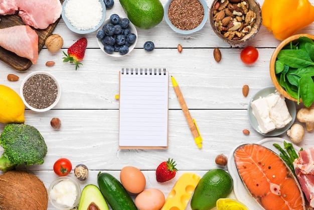 Marco hecho de alimentos saludables, dieta cetogénica baja en carbohidratos con cuaderno de papel. productos ricos en grasas buenas