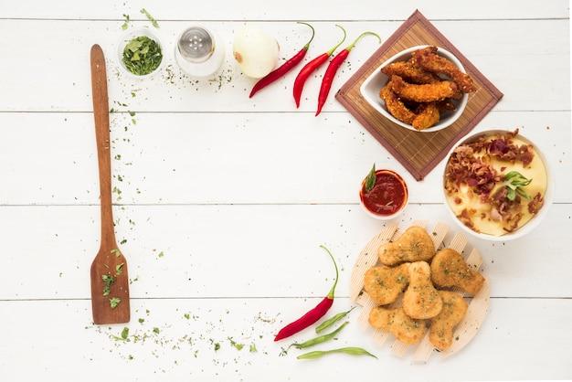 Marco hecho de artículos de cocina, especias, verduras y carne de pollo.