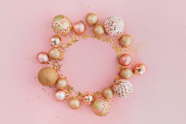 Marco hecho con brillos y bolas de árbol de navidad dorado sobre fondo rosa pálido. concepto festivo.