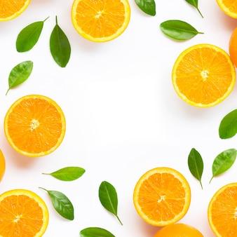Marco hecho de cítricos naranja fresca con hojas aisladas sobre fondo blanco.