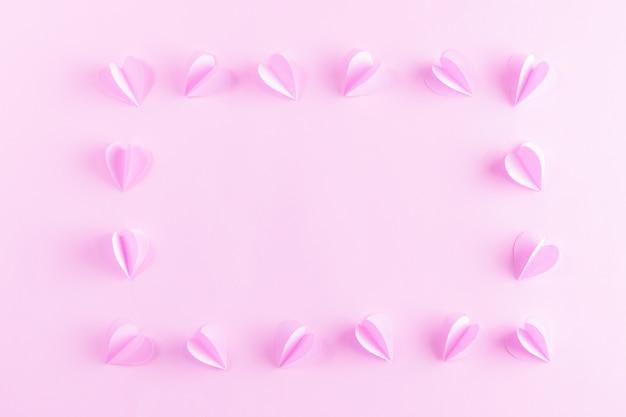 Marco hecho de corazones de color rosa sobre fondo de papel de color rosa pastel. día de san valentín