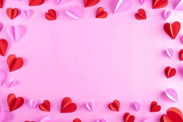 Marco hecho de corazones rosados y rojos sobre fondo rosa pastel. día de san valentín
